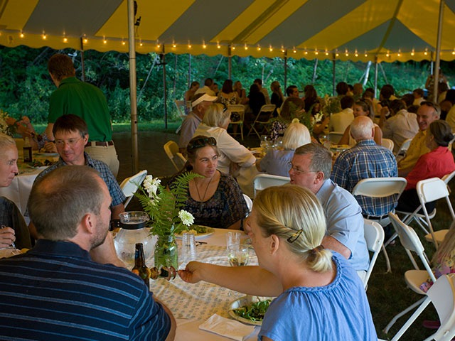 Wedding reception group eating at tables under tent